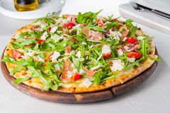 Selective focus Close up Delicious Pizza with hamon and cherry tomato slices, parmezan cheese and arugula on the wooden board on t Royalty Free Stock Photo