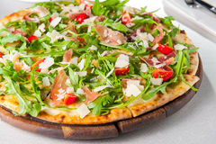 Selective focus Close up Delicious Pizza with hamon and cherry tomato slices, parmezan cheese and arugula on the wooden board on t Stock Photo