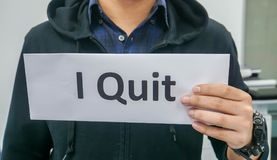 Close up man in black jacket holds paper of I quit for resignation in office. Selective focus close up man in black jacket holds paper of I quit for resignation royalty free stock images