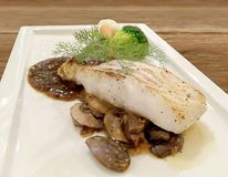Selective focus closeup on Grilled Snapper fish stake. Selective focus closeup on Grilled Snapper fish stake with mushroom Sauce and fresh green vegetable in Stock Photo