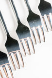 Selective focus closeup macro metal shiny forks lined up over white background Stock Photography