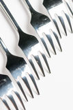 Selective focus closeup macro metal shiny forks lined up over white background Royalty Free Stock Photography