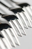 Selective focus closeup macro metal shiny forks lined up over white background Royalty Free Stock Images