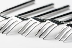 Selective focus closeup macro metal shiny forks lined up over white background Stock Images