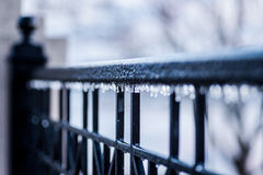 Selective focus closeup view of nice black wrought iron fence with tiny icicles hanging from railing Royalty Free Stock Images