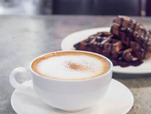 Selective focus coffee  and blur chocolate waffle, cement backg Royalty Free Stock Photo