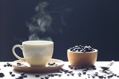 Selective focus of Coffee cup and beans with smoke rising on dar royalty free stock photo