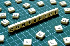 Selective focus of Consensus word made of square letter block on green square mat background.  royalty free stock images