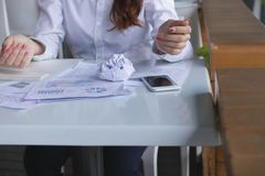 Selective focus on crumpled paper on the desk with paperwork or charts and frustrated employee feeling stress in office. Selective focus on crumpled paper on Royalty Free Stock Photos