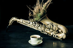 Selective focus on cup of coffee with vintage saxophone and dry field flowers Stock Photos