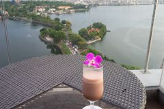 Selective focus on cup of juice fruit against aerial scene of cityscape with lake. Concept of leisure time having drink outdoor, o stock images