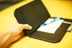 Selective focus customer hand receive bill payment receipt in black leather folder holder tray on yellow wooden table background. In restaurant, shopping mall royalty free stock photography