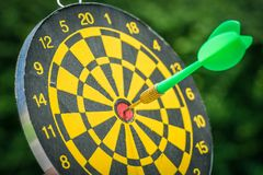 Selective focus on a dart pin in the center of dartboard with gr Stock Image