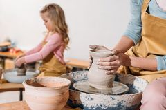 selective focus of daughter making ceramic pot on pottery wheel with mother stock image