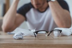Selective focus of depressed student at table with crumpled papers and eyeglasses. On foreground stock photos
