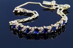 Selective focus of diamond with sapphire bracelet on glossy dark Royalty Free Stock Photos