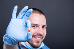 Selective focus of doctor wearing scrubs holding one pill Stock Image