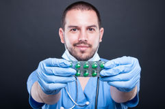 Selective focus of doctor wearing scrubs holding tablets. Blister and smiling on black background Stock Image