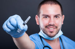 Selective focus of doctor wearing scrubs holding vaccine injecti. On and smiling on black background Stock Photos