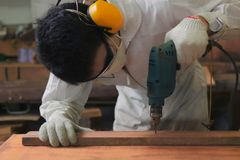 Selective focus on electric drill work on wooden board with hands of young carpenter in carpentry workshop. Selective focus on electric drill work on wooden Royalty Free Stock Image