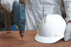 Selective focus on electric drill work on wooden board with hands of young carpenter in carpentry workshop. Selective focus on electric drill work on wooden Royalty Free Stock Photos