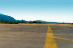 Selective focus on an empty airfield runway with yellow direction lines. Royalty Free Stock Image