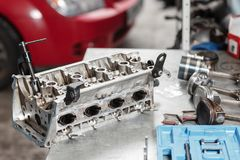 Selective focus. Engine Block on a repair stand with Piston and Connecting Rod of Automotive technology. Blurred red car Royalty Free Stock Image