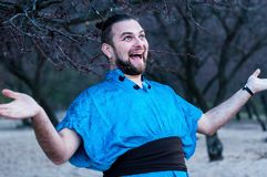 Selective focus of excited laughing bearded man in blue kimono standing with outstretched arms looking awa royalty free stock photo