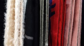 Selective focus. Fabric texture closeup . A row of scarfs hanging from rail. Looks colourful and abstract . Woven stock photos