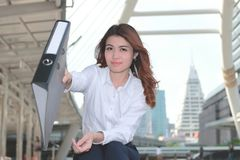 Selective focus on face of attractive young Asian secretary woman holding document folder and smiling at outside office.  Stock Photography