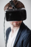 Selective focus on face. Handsome man wearing virtual reality glasses isolated a gray background. Handsome man wearing virtual reality glasses isolated on a gray stock photo