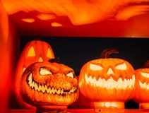 The selective focus on the face of an orange scary pumpkin with Stock Photography