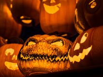 The selective focus on the face of an orange scary pumpkin with Royalty Free Stock Photos