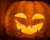 The selective focus on the face of an orange scary pumpkin with Stock Photos