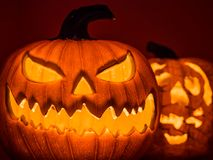 The selective focus on the face of an orange scary pumpkin with Stock Images