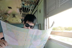 Selective focus on face of young Asian hipster exploring location on the map in the train.Shallow depth of field. Selective focus on face of young Asian hipster Stock Photos