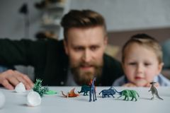 selective focus of father and cute little son looking at arranged toy dinosaurs on tabletop together