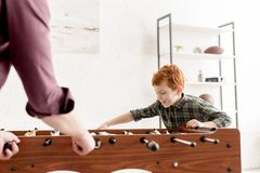 Selective focus of father and cute smiling son playing table football together. At home royalty free stock photo