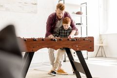 Selective focus of father and son playing table football together. At home royalty free stock photo