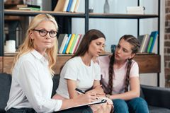 Selective focus of female counselor with clipboard looking at camera while teenage girl. Cheering up depressed mother on therapy session royalty free stock photo