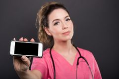 Selective focus of female doctor holding black screen smartphone. On black background with copypsace advertising area Stock Photos