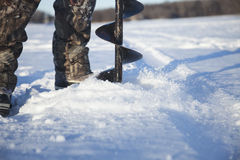 Selective focus fisherman drilling hole in ice with auger Stock Photography