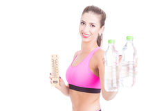 Selective focus of fit woman holding water and thermometer Stock Images