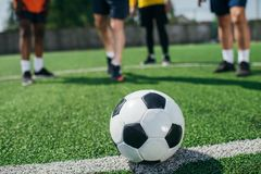 selective focus of football ball and multicultural elderly men on green Stock Photos