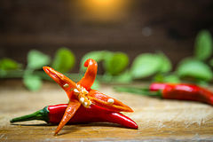 Selective focus on Fresh red hot chili peppers with wooden and green leaves background.  Royalty Free Stock Photography