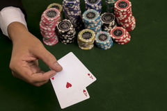 Selective focus at gamlber holding a pair of red aces and chips stock image