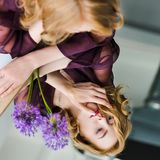 Selective focus of girl looking at reflection while lying on mirror with purple flowers stock images