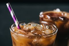 selective focus of glass of cold iced coffee with straw on dark background royalty free stock photos