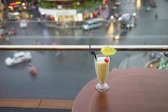 Selective focus on glass of juice against street cityscape on background. Concept of spending leisure time on cafe to enjoy city v Stock Images