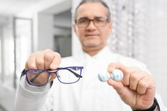 Selective focus of glasses and lens in hands of male oculist stock photos